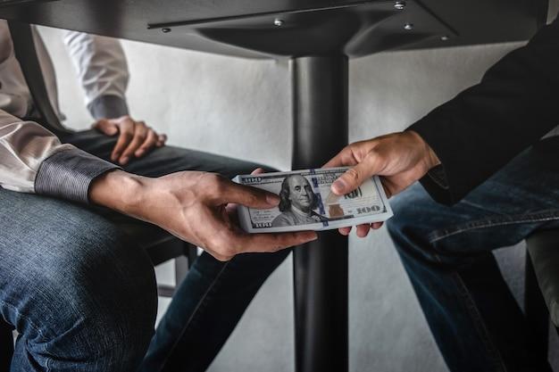 Gli uomini d'affari ricevono bustarelle sotto il tavolo agli uomini d'affari per dare successo al contratto Foto Premium