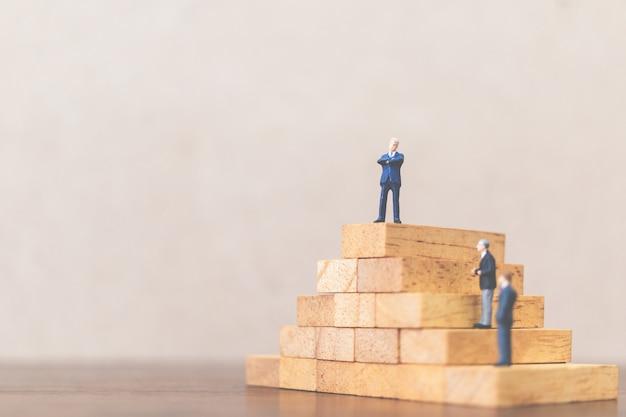 Uomo d'affari che sta sul blocco di legno, sul concetto di riuscito capo e sul lavoro di squadra di affari Foto Premium