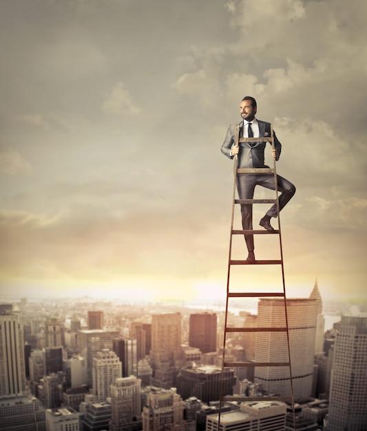 Uomo d'affari sulla cima di una scala Foto Premium