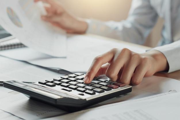 Uomo d'affari utilizzando la calcolatrice per calcolare il bilancio sul tavolo in ufficio Foto Premium