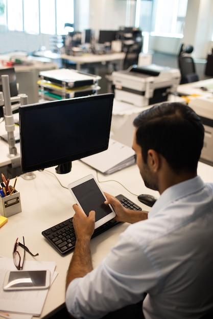 Imprenditore utilizzando tavoletta digitale mentre è seduto alla sua scrivania in ufficio Foto Premium