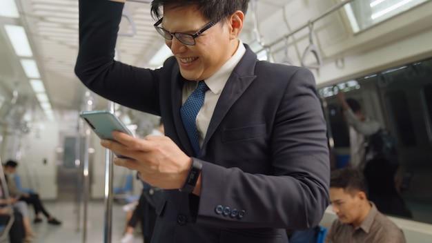 Uomo d'affari utilizzando il telefono cellulare sul treno pubblico. concetto di pendolarismo di stile di vita urbano della città. Foto Premium