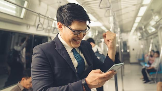 Uomo d'affari utilizzando il telefono cellulare sul treno pubblico Foto Premium