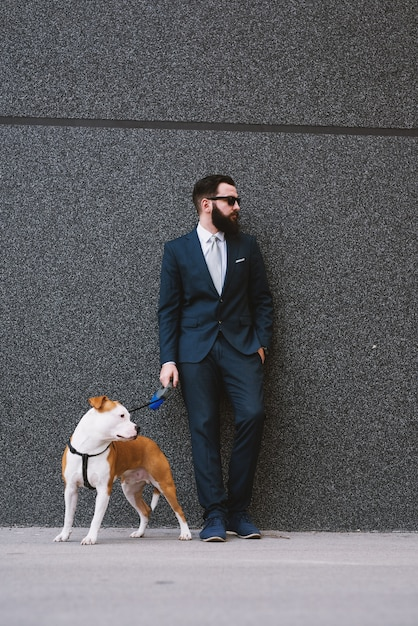 Uomo d'affari che cammina cane in strada. Foto Premium
