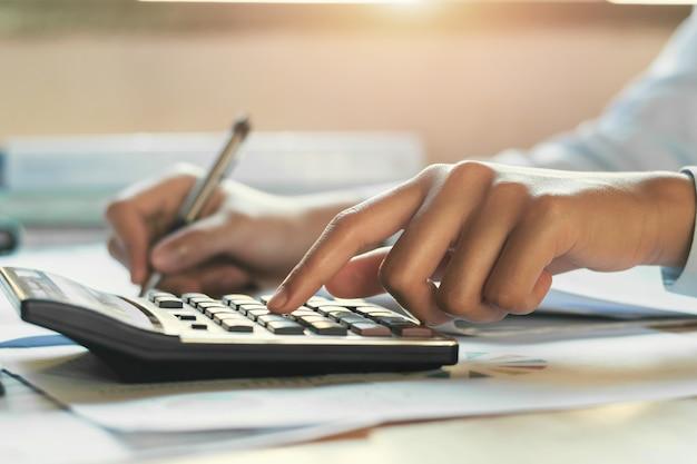 Uomo d'affari che lavora all'ufficio dello scrittorio con per mezzo di un calcolatore, concetto di contabilità di finanza Foto Premium