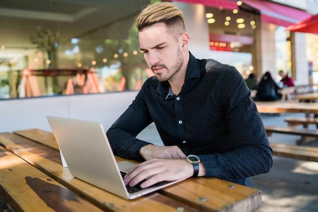 Uomo d'affari che lavora sul suo computer portatile. Foto Premium