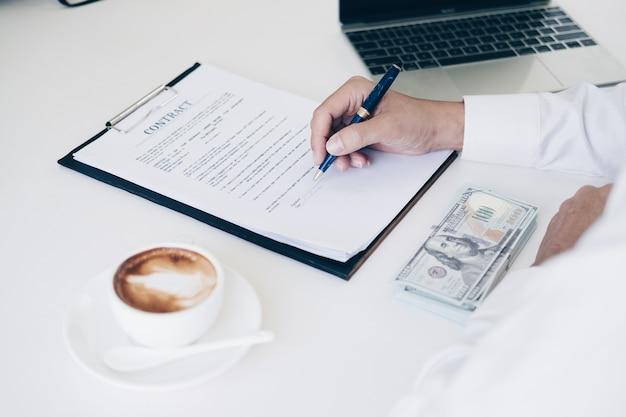 Uomini d'affari che tengono penna per scrivere documento commerciale e foglio di contratto Foto Premium