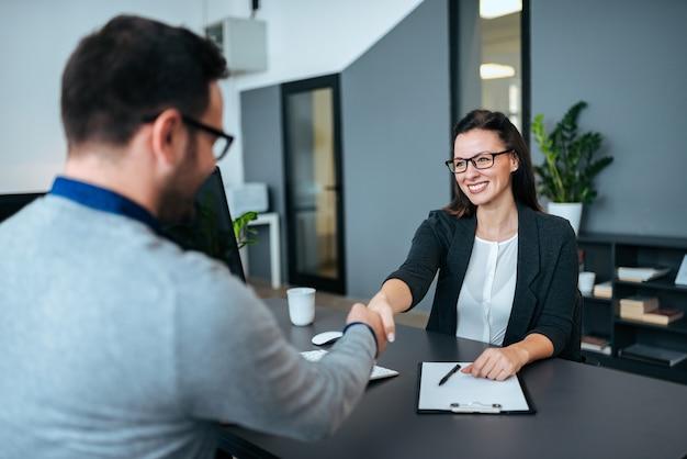 Donna di affari ed uomo d'affari che stringono le mani in ufficio moderno. Foto Premium