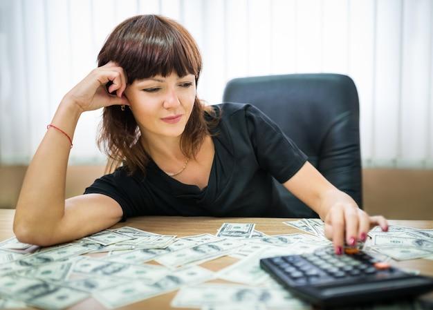 Imprenditrice calcolare il reddito su una calcolatrice Foto Premium