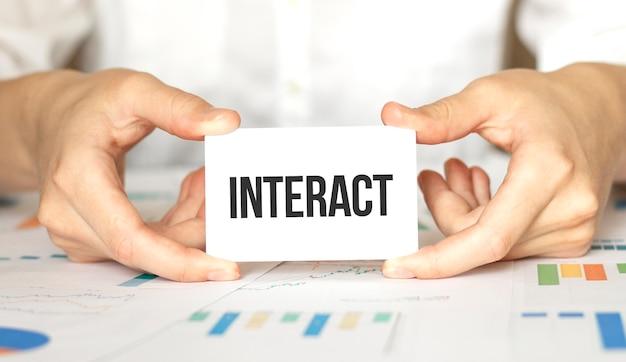 Imprenditrice in possesso di una carta con testo interagisci Foto Premium