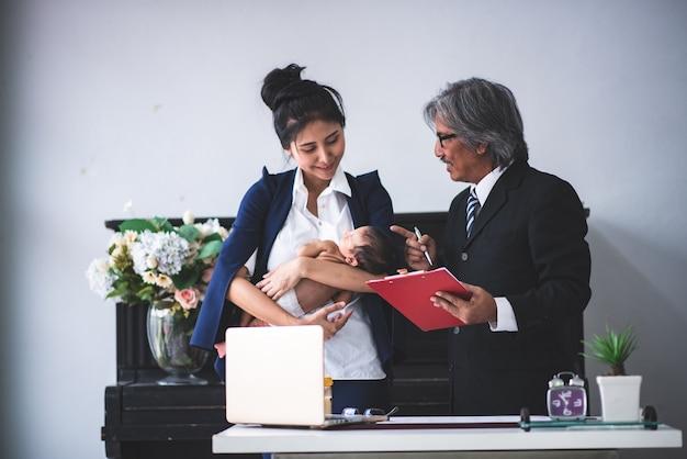 La donna di affari sta funzionando tenendo il suo bambino Foto Premium
