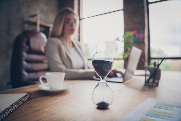 Imprenditrice guardando l'ufficio a clessidra al chiuso Foto Premium