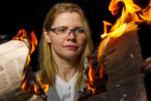 Donna di affari che legge le notizie calde o che legge i prezzi delle azioni di notizie del mercato azionario. rivista burning in mani della donna - concetto di notizie calde e ultime Foto Premium