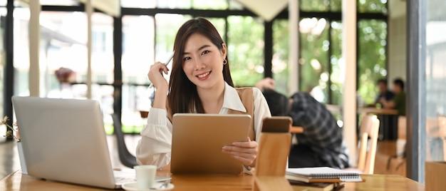 Donna di affari che si siede nella sala riunioni mentre si lavora con tablet e laptop sulla scrivania in legno. Foto Premium