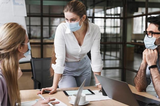 Imprenditrice con mascherina medica tenendo una riunione professionale Foto Premium