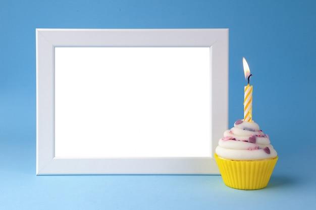 Torta con candela e cornice per foto sul primo piano sfondo blu Foto Premium