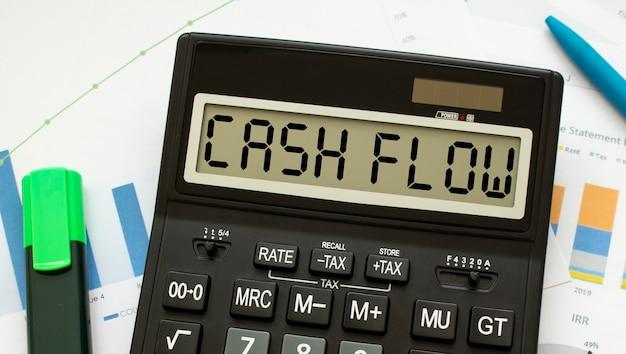 Una calcolatrice etichettata flusso di cassa si trova sui documenti finanziari in ufficio. concetto di affari. Foto Premium
