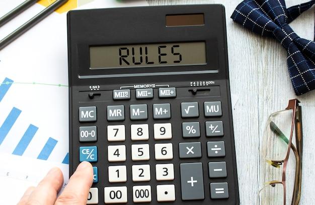 Una calcolatrice con l'etichetta regole giace sui documenti finanziari in ufficio. concetto di affari Foto Premium