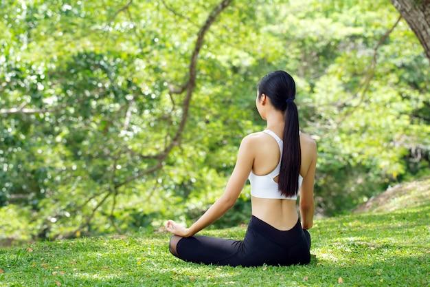 Calma e relax, le donne asiatiche meditano mentre praticano lo yoga nel parco all'aperto. concetto di libertà felicità della donna. immagine tonica vita sana Foto Premium