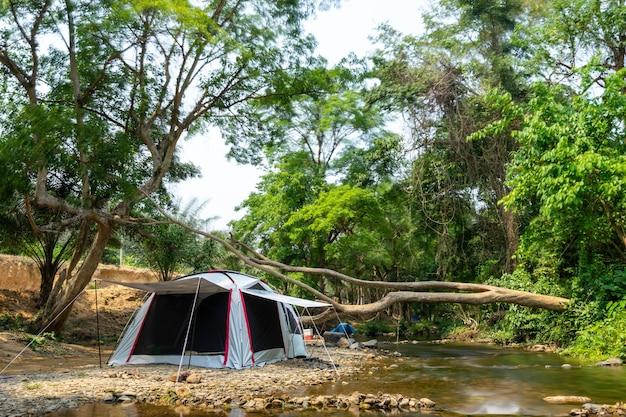 Campeggio e tenda vicino al fiume nel parco naturale Foto Premium