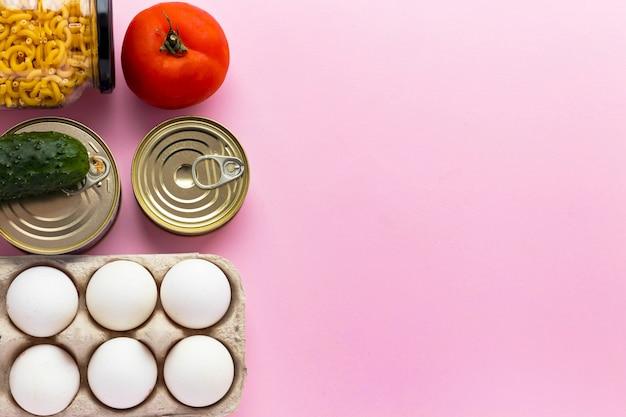 Conserve, verdure fresche, pomodoro e cetriolo, uova di chichen e pasta in barattolo di vetro su sfondo rosa Foto Premium
