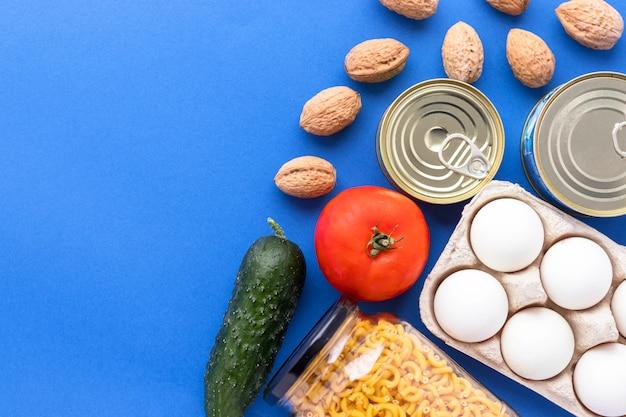 Conserve, noci, verdure fresche, pomodoro e cetriolo, uova di chichen e pasta in barattolo di vetro su sfondo blu Foto Premium