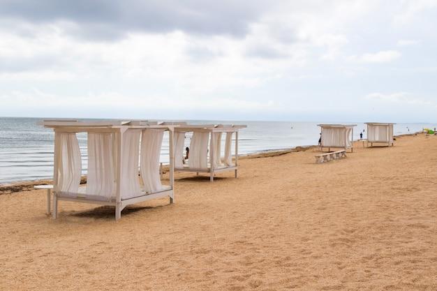Baldacchini con tende bianche sulla spiaggia di sabbia dal mare. nuvole grigie. Foto Premium