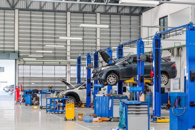 Auto in attrezzature di sollevamento nel garage in riparazione e riparazione Foto Premium