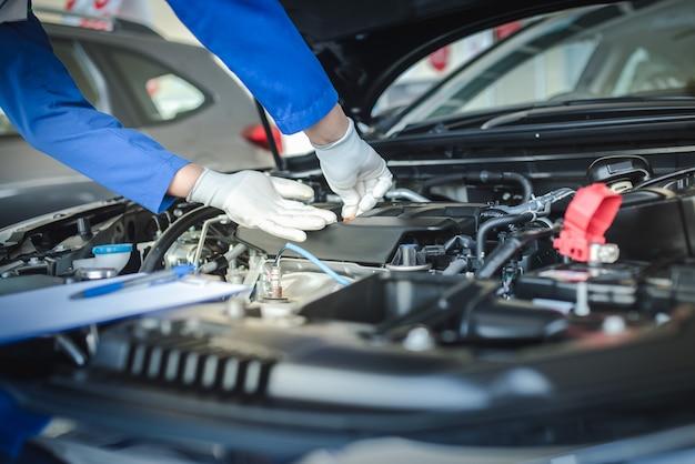 Il personale del meccanico automobilistico sta alzando l'indicatore di livello dell'olio per controllare il livello dell'olio. per controllare le condizioni dell'auto Foto Premium