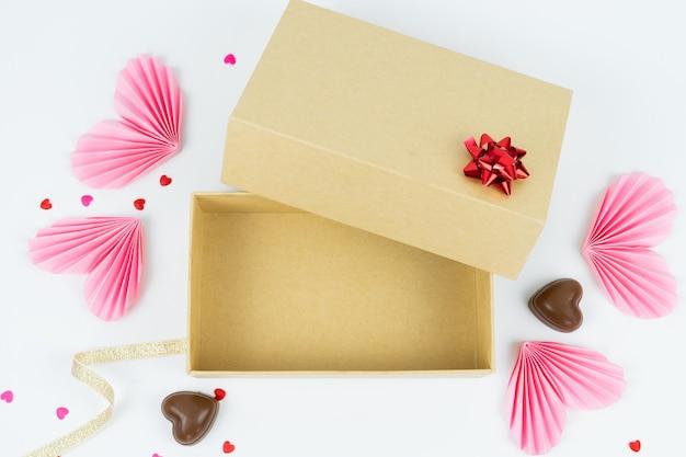Scatola di cartone con cuori di carta e cioccolatini concetto di san valentino Foto Premium