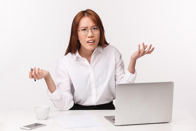 Concetto di imprenditori di carriera, lavoro e donne. ritratto del primo piano della donna di affari asiatica confusa e frustrata che si siede alla scrivania con l'espressione perplessa, chieda perché o cosa, scrollando le spalle perplesso Foto Premium