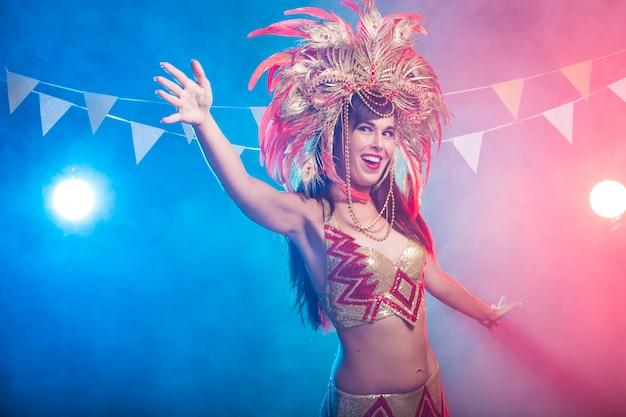 Carnevale, danza del ventre e concetto di vacanza - bella ballerina di samba femminile che indossa un costume d'oro e sorridente. Foto Premium