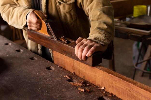 Carpentiere che lavora sulla vista laterale di falegnameria Foto Premium