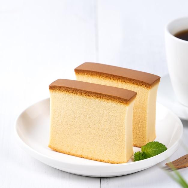 Castella (kasutera) - cibo delizioso delizioso pan di spagna affettato giapponese sul piatto bianco sul tavolo in legno bianco rustico, close up, concetto di design dello spazio della copia. Foto Premium