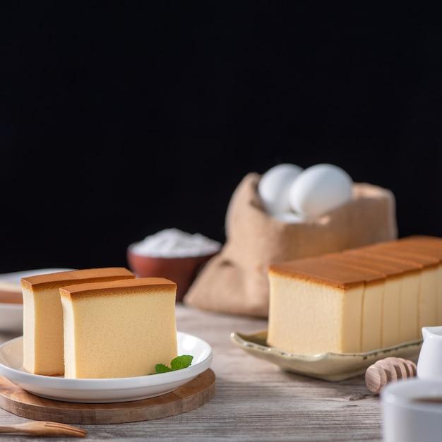 Castella kasutera delizioso giapponese a fette di pan di spagna cibo sulla piastra bianca su tavola in legno rustico vicino mangiare sano spazio copia design Foto Premium
