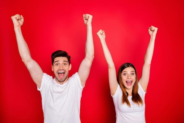 Coppie casuali che propongono contro il muro rosso Foto Premium