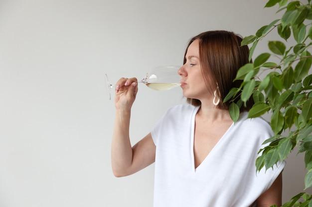 Sommelier caucasico della ragazza del brunette che beve vino bianco dal vetro Foto Premium