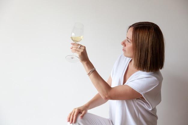 Sommelier caucasico della ragazza del brunette che tiene bicchiere di vino bianco Foto Premium