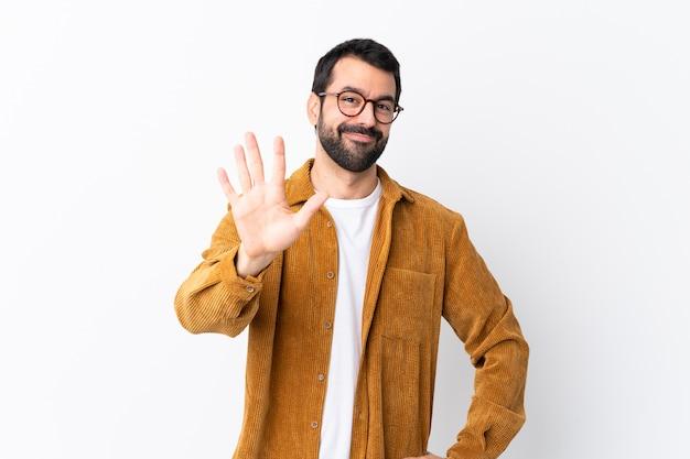 Caucasico bell'uomo con la barba che indossa una giacca di velluto a coste su bianco contando cinque con le dita Foto Premium