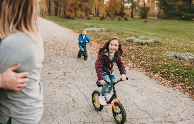 Bambini caucasici in sella alle loro biciclette e sorridendo felicemente ai loro genitori durante una passeggiata insieme nel parco Foto Premium