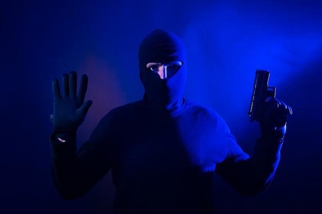 Ladro caucasico con le mani alzate e la pistola. include le luci della polizia. Foto Premium