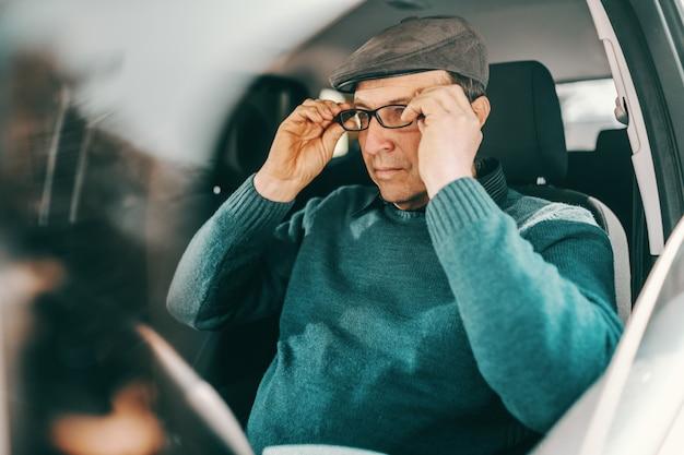 Uomo senior caucasico con il cappuccio sulla testa che mette gli occhiali mentre sedendosi in un'automobile Foto Premium