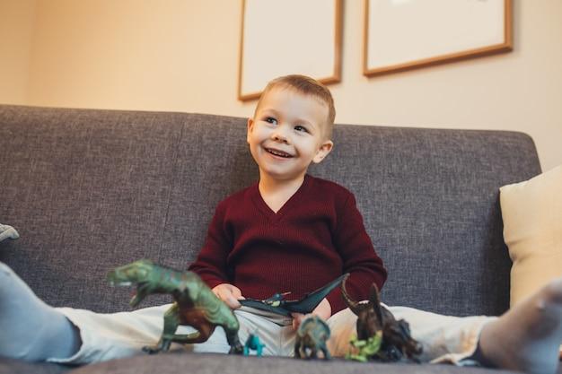 Piccolo ragazzo caucasico seduto sul divano e gioca con i suoi giocattoli di dinosauro mentre guarda i suoi genitori Foto Premium