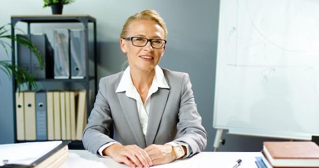 Caucasica sorrise donna con gli occhiali seduto in ufficio e parlando tramite webcam, videochattare e istruire gli affari. allenatore femminile che registra video blog. videochat di blogger. coaching in linea di affari. Foto Premium