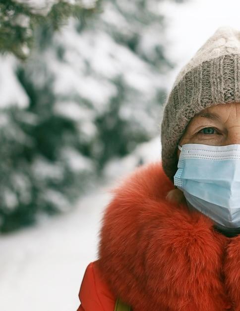 La donna caucasica indossa la maschera medica guardando la telecamera in strada della città nel periodo invernale. sicurezza in luoghi pubblici durante l'epidemia di coronavirus. Foto Premium