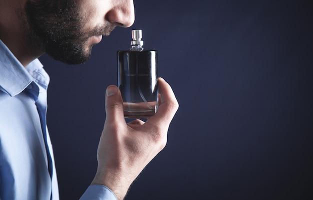 Giovane caucasico che sente l'odore del profumo. Foto Premium