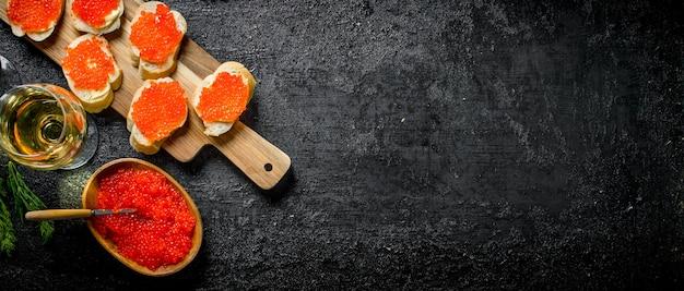 Caviale nella ciotola, panini con caviale rosso e vino. sulla superficie rustica nera Foto Premium
