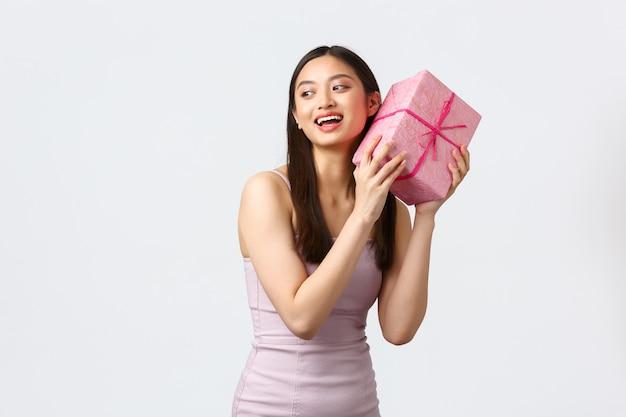 Celebrazione, festa e concetto di vacanze. eccitata ragazza asiatica carina felice in abito da sera, scuotendo la confezione regalo per indovinare cosa c'è dentro Foto Premium