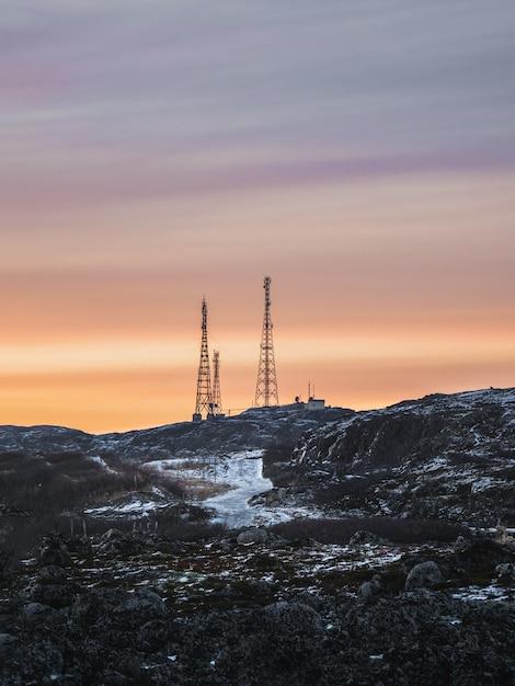 Torri cellulari nelle colline innevate nella tundra. bel tramonto paesaggio collinare dell'artico Foto Premium