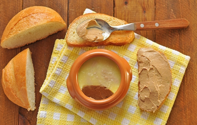 Pentola e cucchiaio in ceramica con patè e pane tostato su un tovagliolo. sfondo di legno Foto Premium